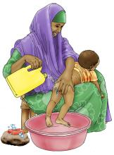 Sanitation - Woman washing baby's bottom - 01 - Kenya Dadaab